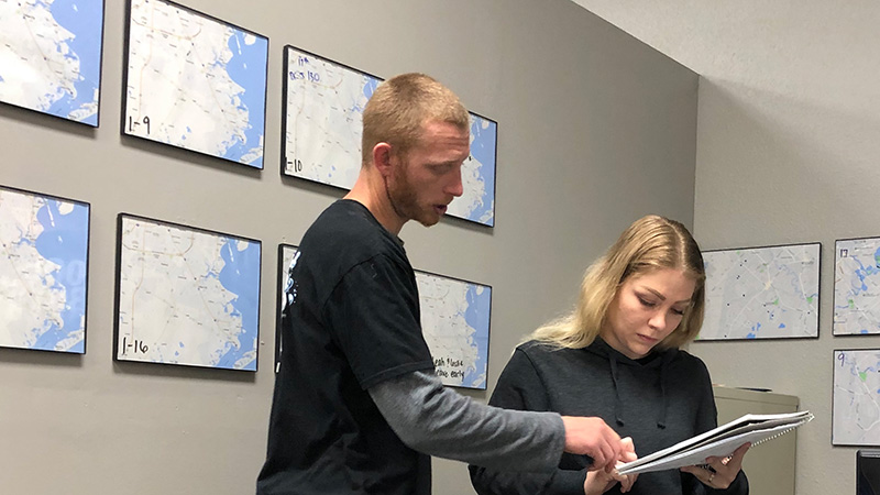 Justin and Leah going over route changes in The Pool Boys office