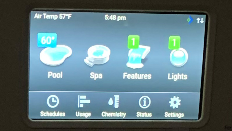 Pentair Intelliflo control panel display with top of screen showing Air Temp 57F, 5:48 pm, and icons labeled Pool, Spa, Features, Lights, Schedules, Usage, Chemistry, Status, Settings